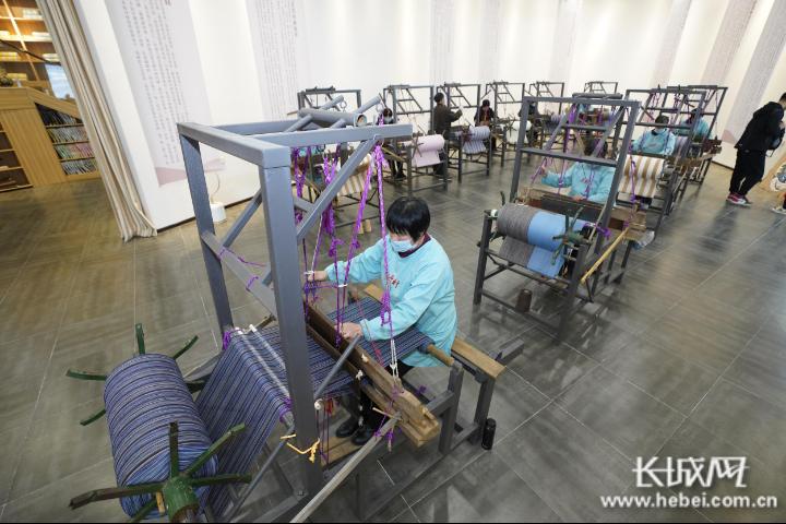 """原村博物馆的""""织娘""""们正在织布。长城网记者 周黎燕 摄"""