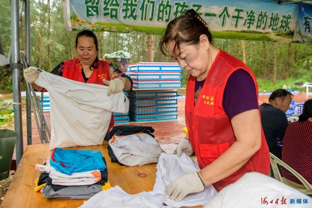 10月28日上午,两名候鸟老人在白沙门环保教育站将收集来的废弃衣物叠好。
