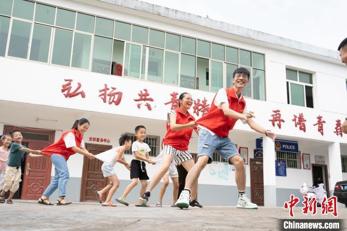"""今年7月28日,新余市观巢镇共青村""""留守儿童之家"""",孩子们和青年志愿者一起做游戏。 赵春亮 摄"""