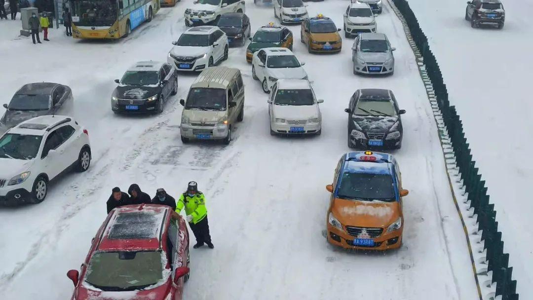 交警帮助打滑车辆推车。哈尔滨日报手机记者 齐保国 摄