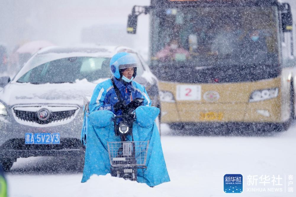 ↑11月19日,在哈尔滨市中山路,送餐员在雪中骑车。新华社记者 王建威 摄