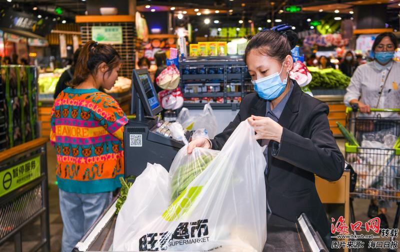 11月18日,海口旺豪超市收银台工作人员使用可降解环保袋为顾客打包商品。记者 康登淋 摄