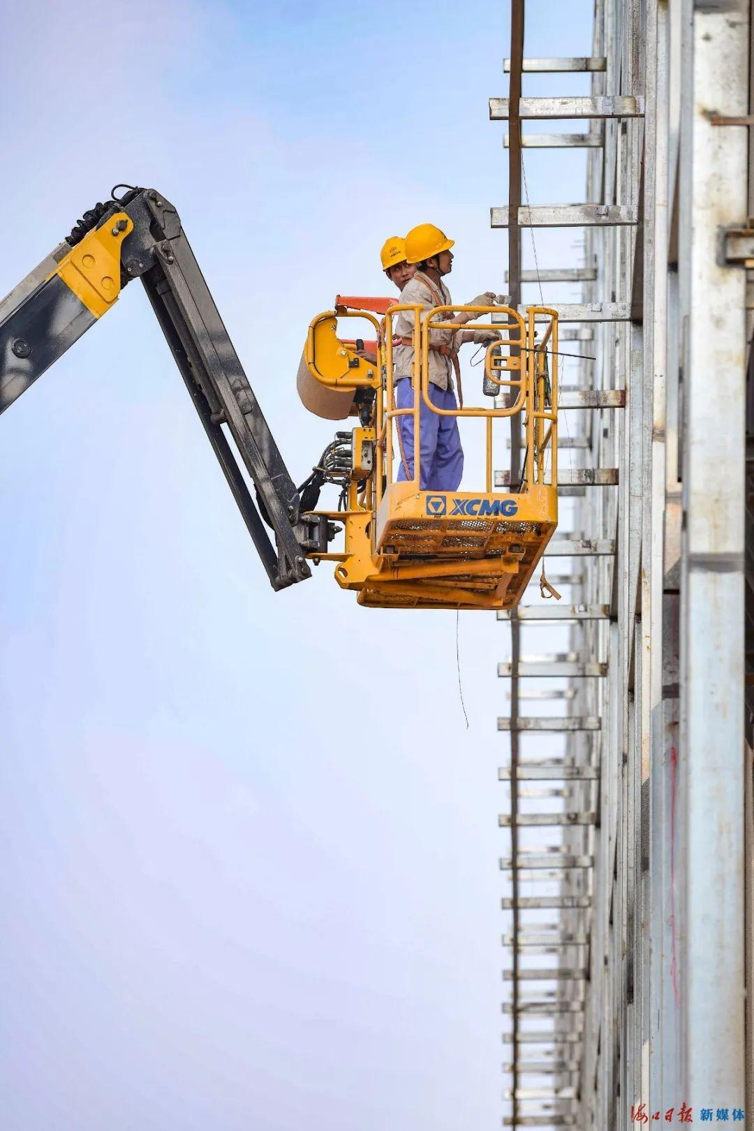 11月2日,在位于海口江东新区临空经济区的美兰空港一站式飞机维修基地项目工地,机械轰鸣,工人在安装厂房幕墙。海口日报记者 王程龙 摄