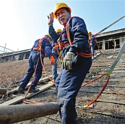 工人们小心拆下轮机厂房一百多年的屋瓦