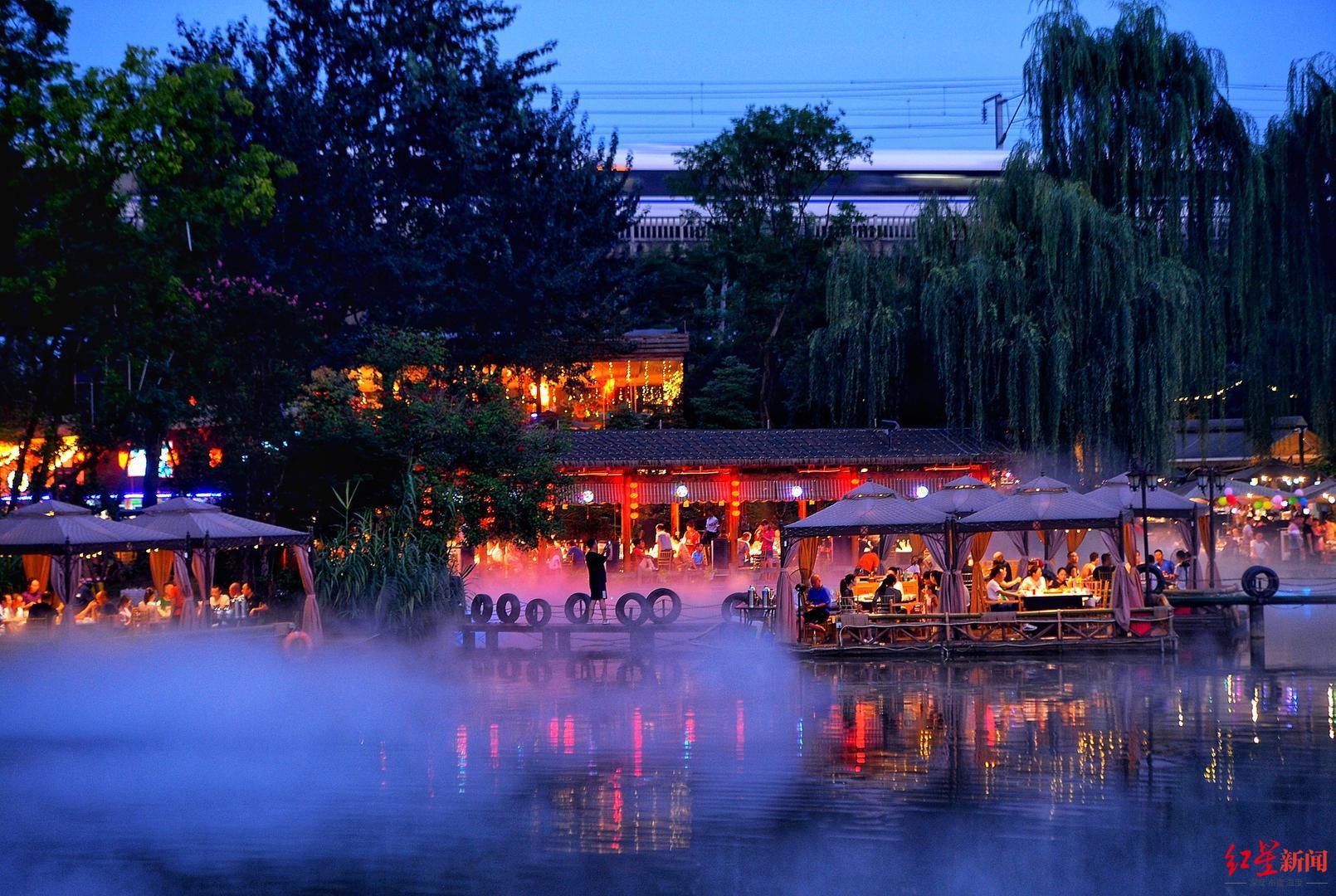 ▲食客在湖边吃火锅,高铁从上方驶过。