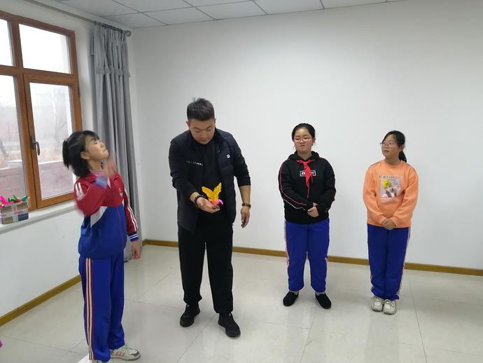 志愿者在教孩子们踢毽球