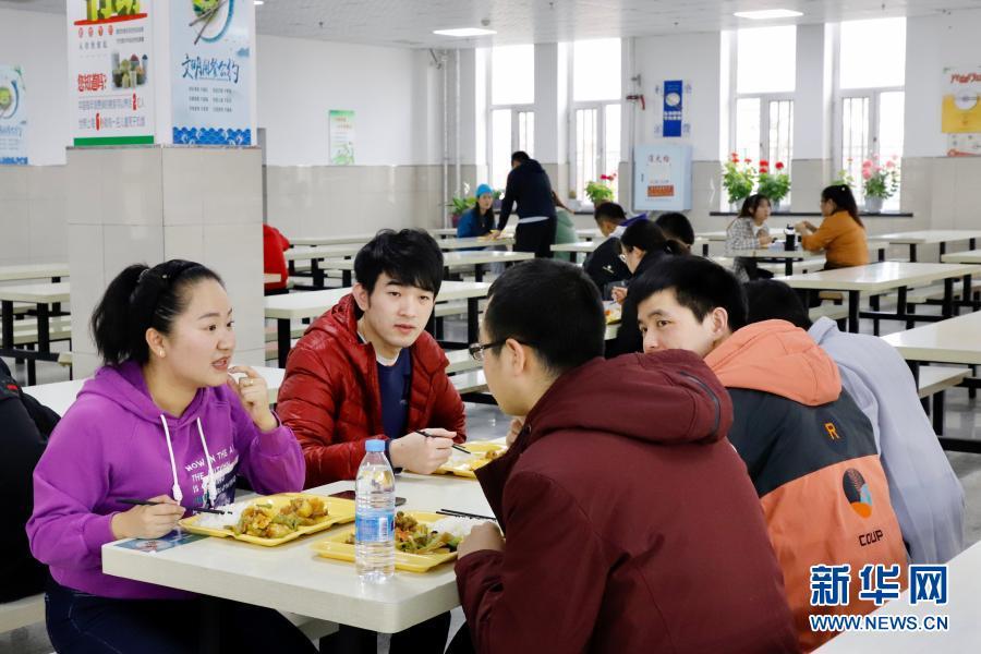 11月18日,在黑龙江绥化学院,李泽卉(左一)与学生一起吃饭。