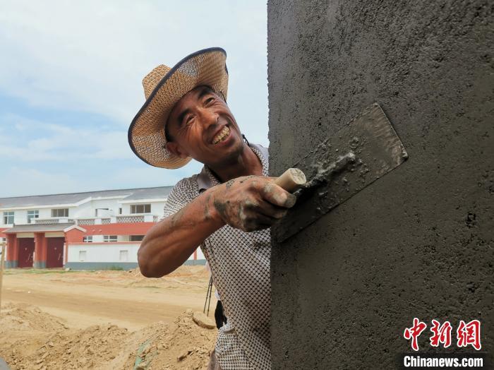 资料图。图为,山东菏泽市鄄城县旧城镇村民在旧城镇实施的滩区改造工程项目打工,建设自己未来的新房。 杨飞 摄