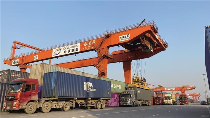 在西安国际港务区铁路集装箱中心站,忙碌的龙门吊依次给货运卡车加装集装箱。