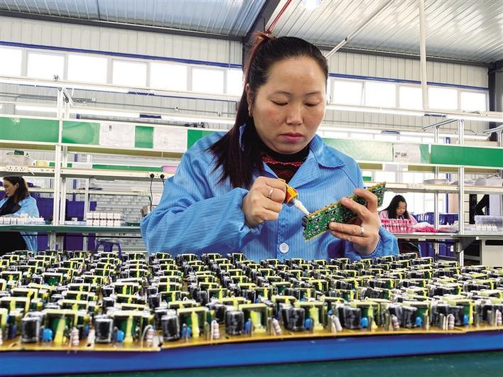在安康市万顺兴电子科技有限公司里,工人正在加工手机充电器。