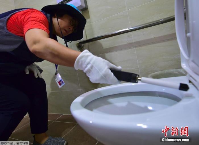 """当地时间2016年10月18日,韩国首尔,首尔""""隐藏相机狩猎""""分队成员在一家博物馆女厕所搜索隐藏摄像头,保护女性如厕安全。"""