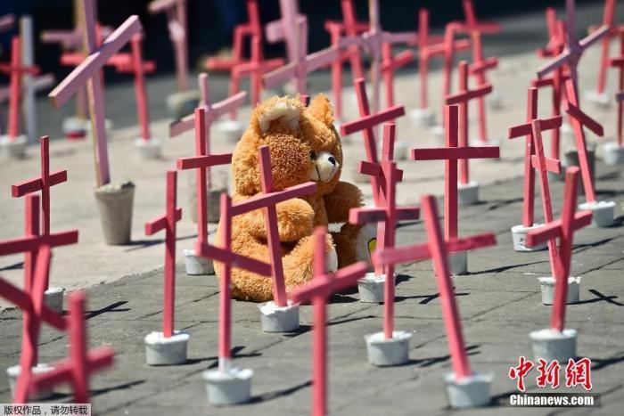 资料图:当地时间2016年3月13日,墨西哥埃克泰佩克民众在市政厅前放置十字架,抗议当地杀害妇女案频发。