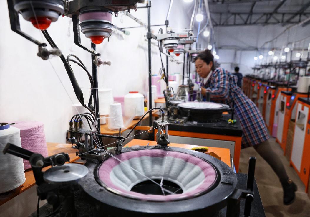 沐洁之家的生产线,机器直接纺织出各种型号的马桶垫。图为工人在调试机器。(摄影:杨子)