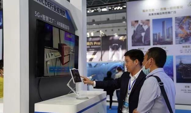 工作人员向嘉宾介绍5G+智慧工厂AR装配指导项目 申蓓/摄