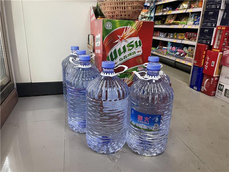 12 月 3 日,长沙上海城小区一家便利店,因为小区停水比较频繁,便利店内摆了一些 大桶水供业主购买。图 / 记者 满延坤