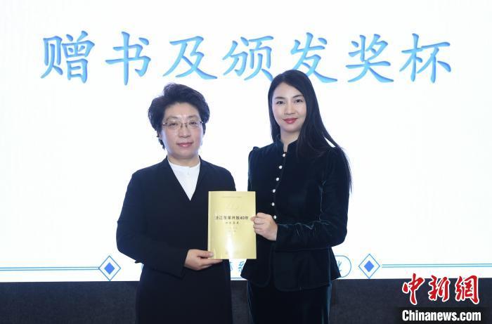 中国新闻社浙江分社常务副社长、总编辑柴燕菲为杨玲玲赠送《浙江改革开放40年口述历史》书籍。 王刚 摄