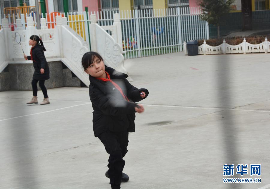 12月1日,在广河县三甲集镇火炬小学的操场上,马梅在课间和同学打羽毛球。新华社记者 颜之宏 摄
