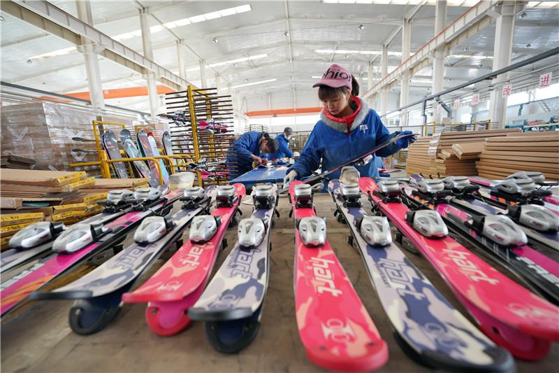 12月5日,张家口京禧体育器材有限公司的工人在生产车间内制作滑雪板。