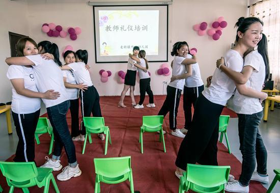 9月9日,江西省吉安市新干县麦镇中心幼儿园支教老师邹小琳(左五)正在对该园幼教老师进行礼仪培训。视觉中国供图