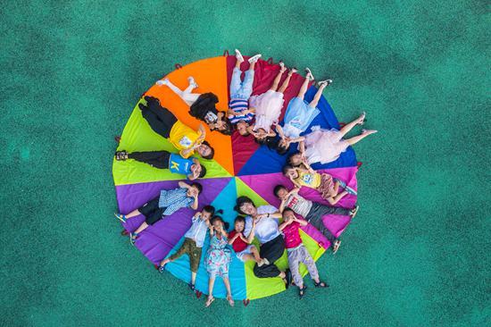 9月9日,江西省吉安市新干县城上乡中心幼儿园支教幼师敖敏慧(黄衣服)和刘智秀(白衣服)正在指导该园幼儿开展降落伞游戏。视觉中国供图