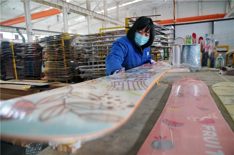 12月5日,张家口京禧体育器材有限公司的工人在生产车间内打磨滑雪板。
