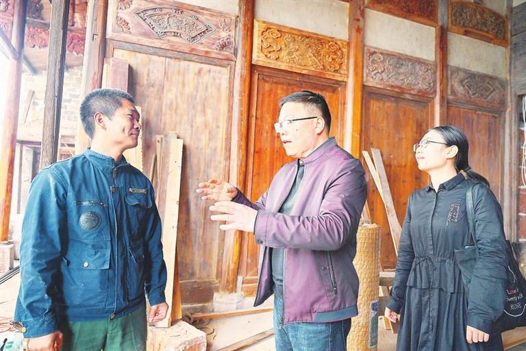 周塘村扶贫帮扶队长姜贵方(中)、帮扶队员金叶(右一),建议艾先元把雕刻产品都配上效果图和编号。