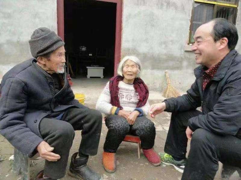 王新奇(右一)到贫困村民家中走访(王曦健 摄)