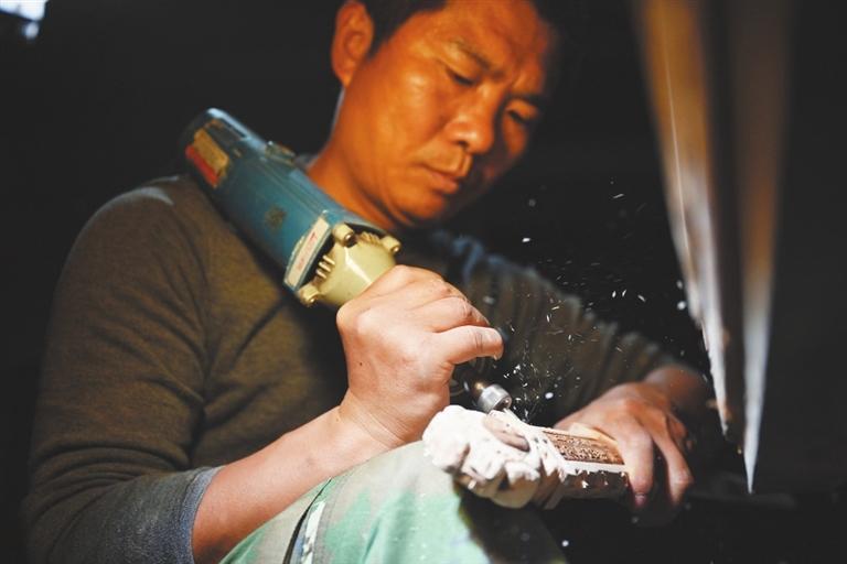 艾先元在灯下精心打磨木雕产品。
