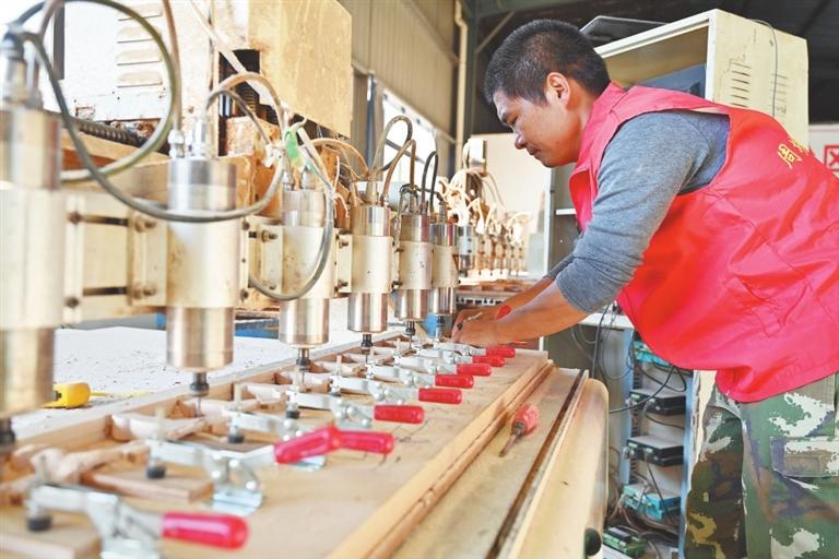 艾先元在扶贫车间数控雕刻机上安装雕刻产品粗坯。