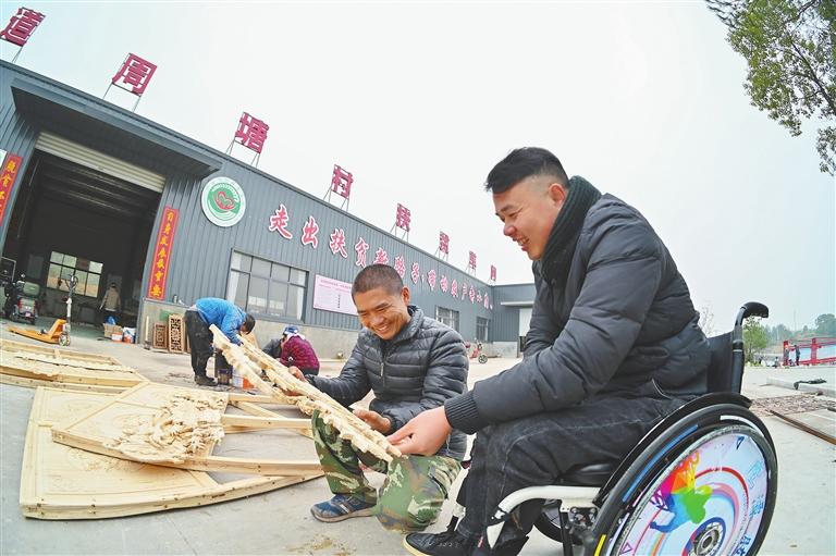 12月7日,在鹰潭市信江新区江北街道周塘村扶贫车间,艾先元(左)向徒弟张智灵讲解机雕木艺技巧。
