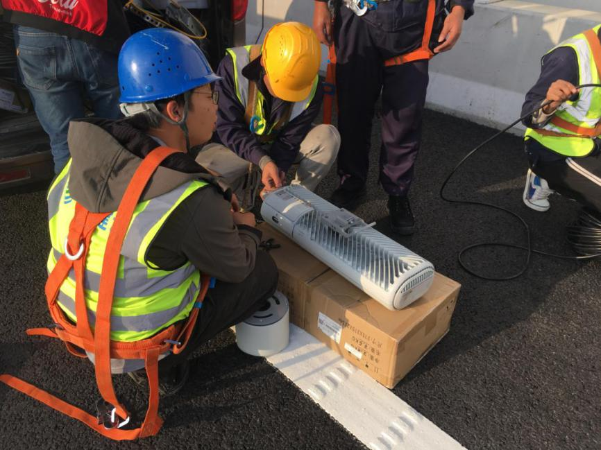 移动网络建设人员正在组装5G一体化设备。