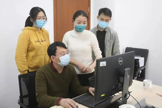 王小莉(后排中二)正在和同事们分析感染者分布特点。 新京报记者 王嘉宁 摄