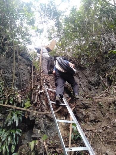 由于地质特点,广西区内的电普建设项目建设难度大,图中移动工作人员在近90度的陡峭山崖上攀爬,搬运杆塔等建设物资。 广西移动供图