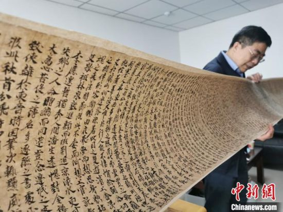 2020年9月底,读者集团敦煌文艺出版社社长展示《敦煌法藏文献》的复制品。(资料图) 闫姣 摄