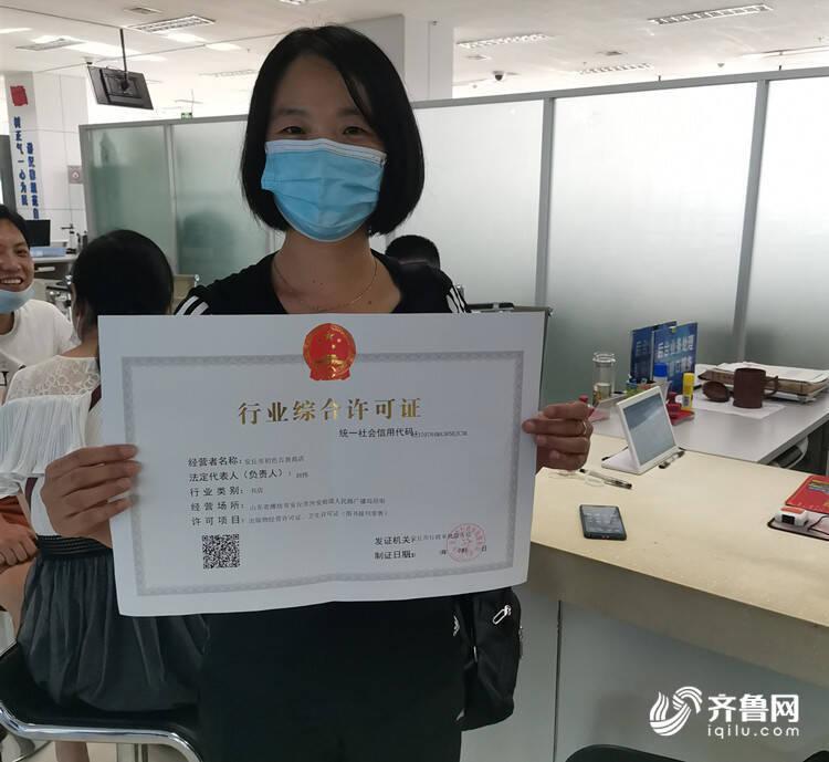 """图/拿到潍坊安丘市行政审批服务局制发的""""行业综合许可证"""",刘女士喜上眉梢。"""