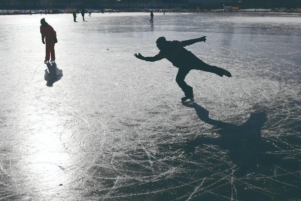 南湖的冰面上,光影中的花样滑冰爱好者。