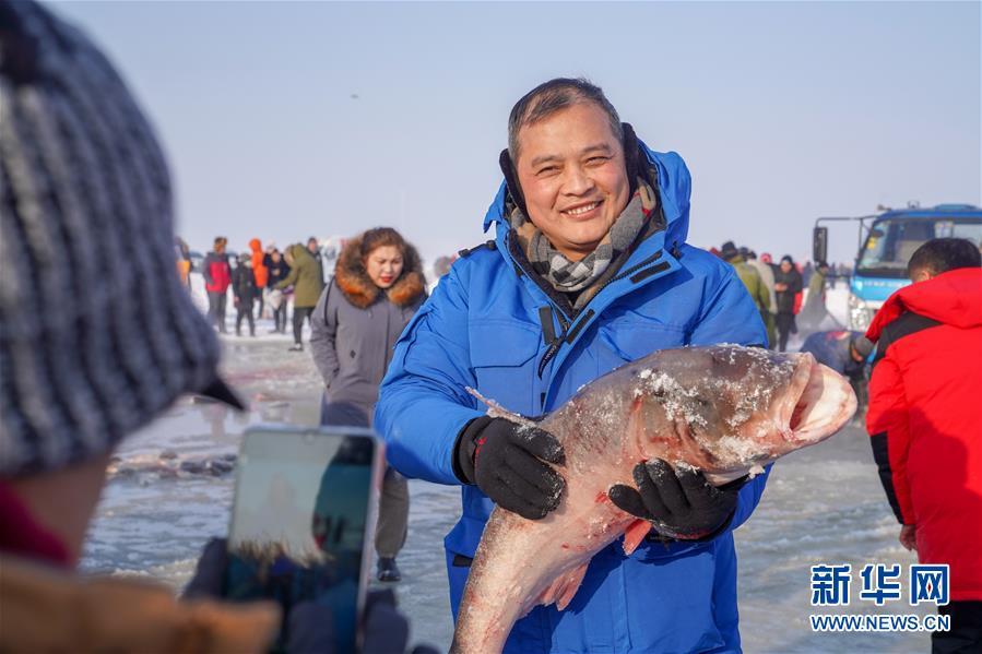 12月27日,在查干湖冰面上,游客在冬捕现场围观。新华社记者 张楠 摄