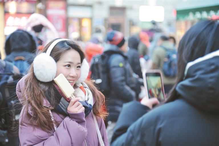 ↑两位来自广东的女孩手拿马迭尔冰棍拍照留念。
