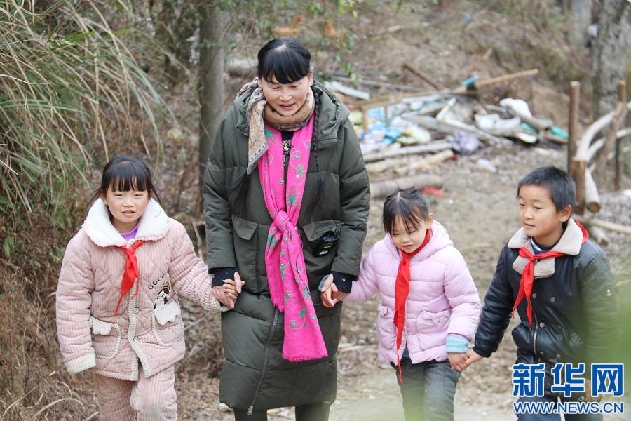 支月英牵着孩子们走在山路上。新华网 发