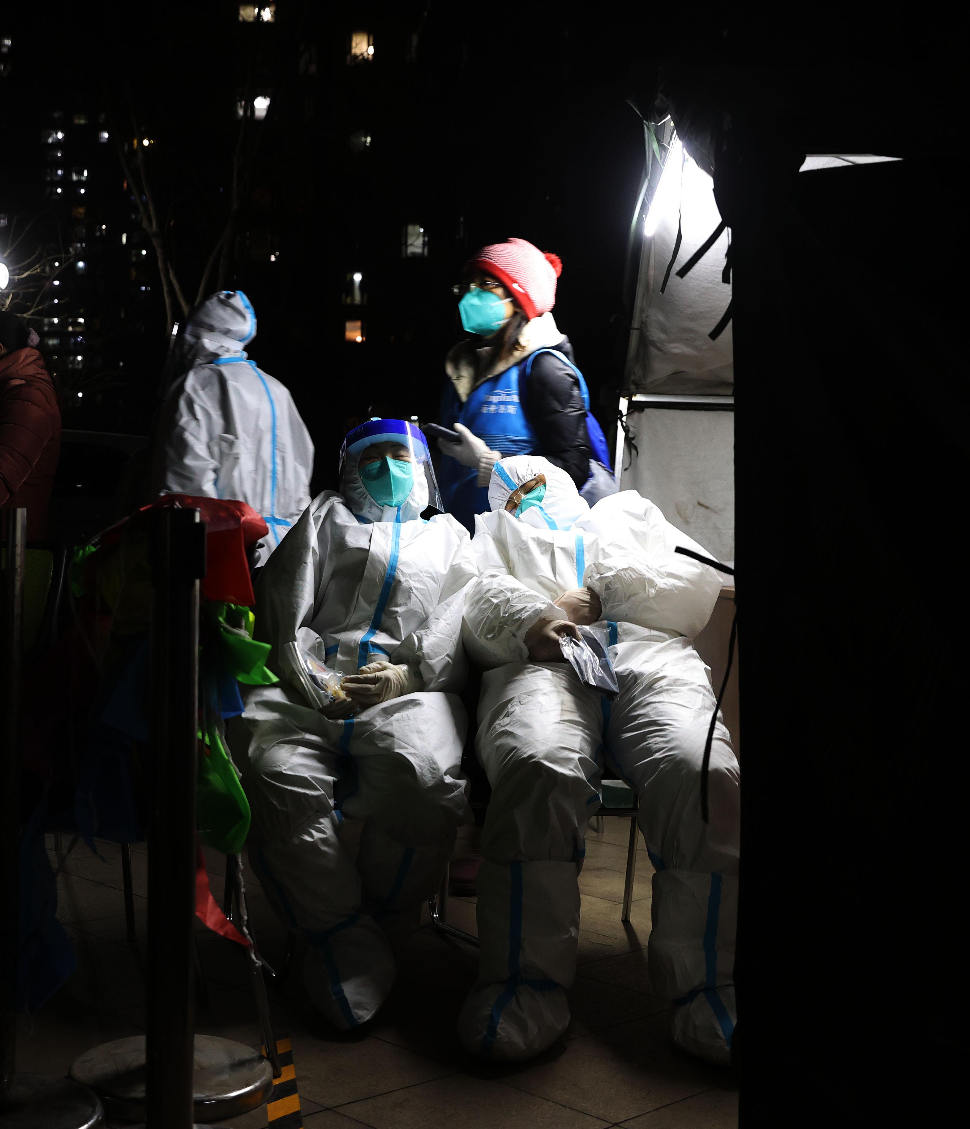 1月12日夜,来自广东深圳核酸检测服务队的采样人员利用检测间隙小憩。