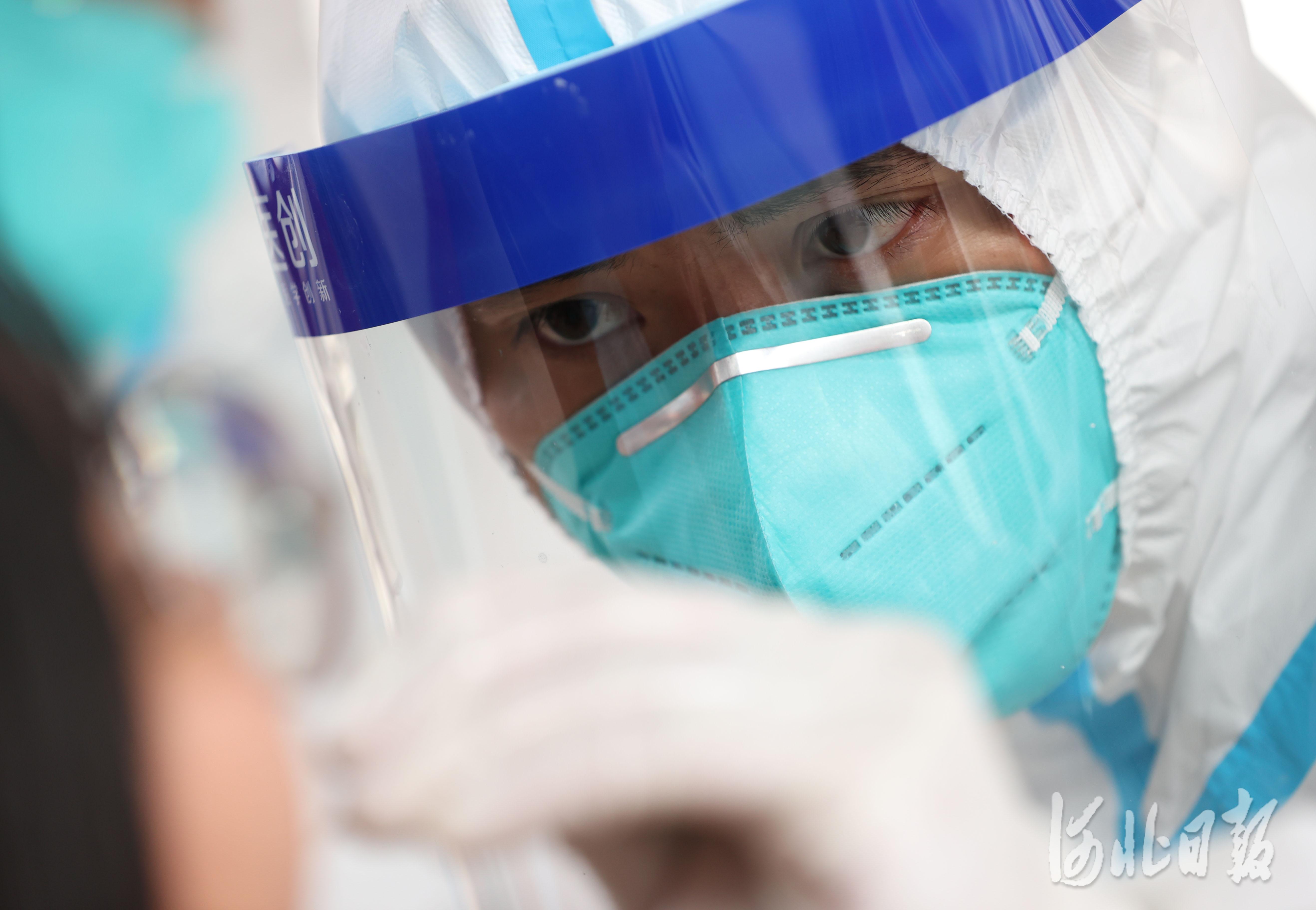 2021年1月12日,来自广东深圳的核酸检测服务队的采样人员邹奇给石家庄市新华区赵陵铺路街道党家庄社区的居民进行核酸检测。
