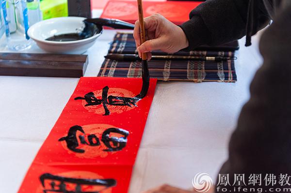 书法家和书法爱好者挥毫泼墨送春联(图片来源:凤凰网佛教 摄影:杨净弘)