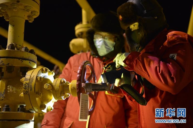 1月6日,采气一厂区域中心监测员刘立伟(右)和采气一厂涩北一号作业区二号站站长焦柏竣(左)在检查设备仪表与管道阀门。新华社记者 张曼怡 摄