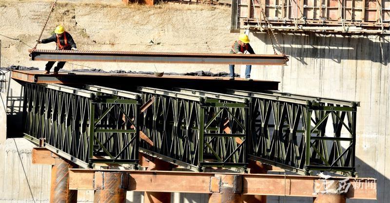 """元月12日,在""""瓷都""""景德镇市昌江河上的景德镇水利枢纽工程现场,建筑工人正借助大型机器设备紧张铺设钢架桥。"""