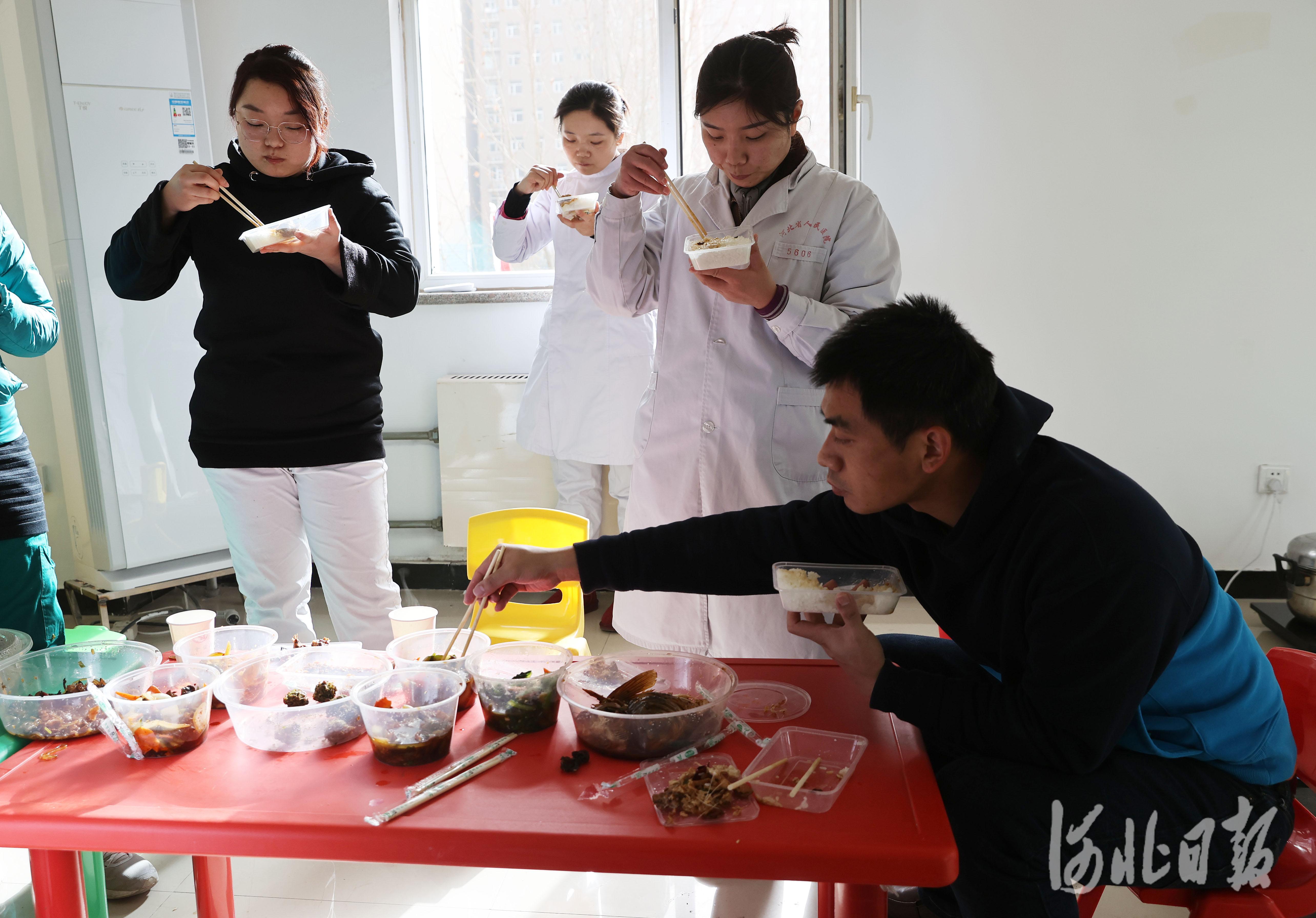 2021年1月12日13时许,来自广东深圳核酸检测服务队的采样人员邹奇(右一)与省人民医院的医务采样人员一起吃午饭。