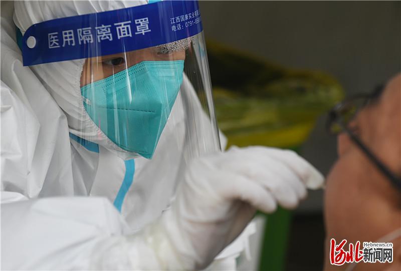 1月12日,来自天津的核酸检测服务队队员在石家庄市新华区星河御城社区为居民进行核酸检测采样。 河北日报记者 史晟全摄