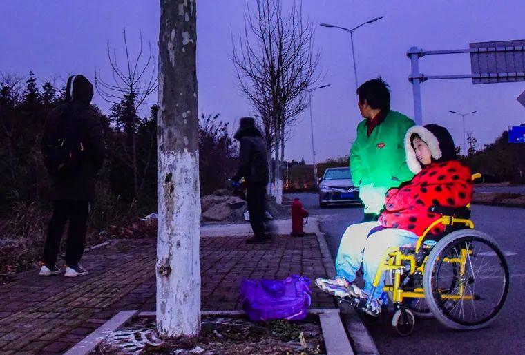 奶奶张桂月和坐着轮椅的婷婷在寒风中等待校车的到来
