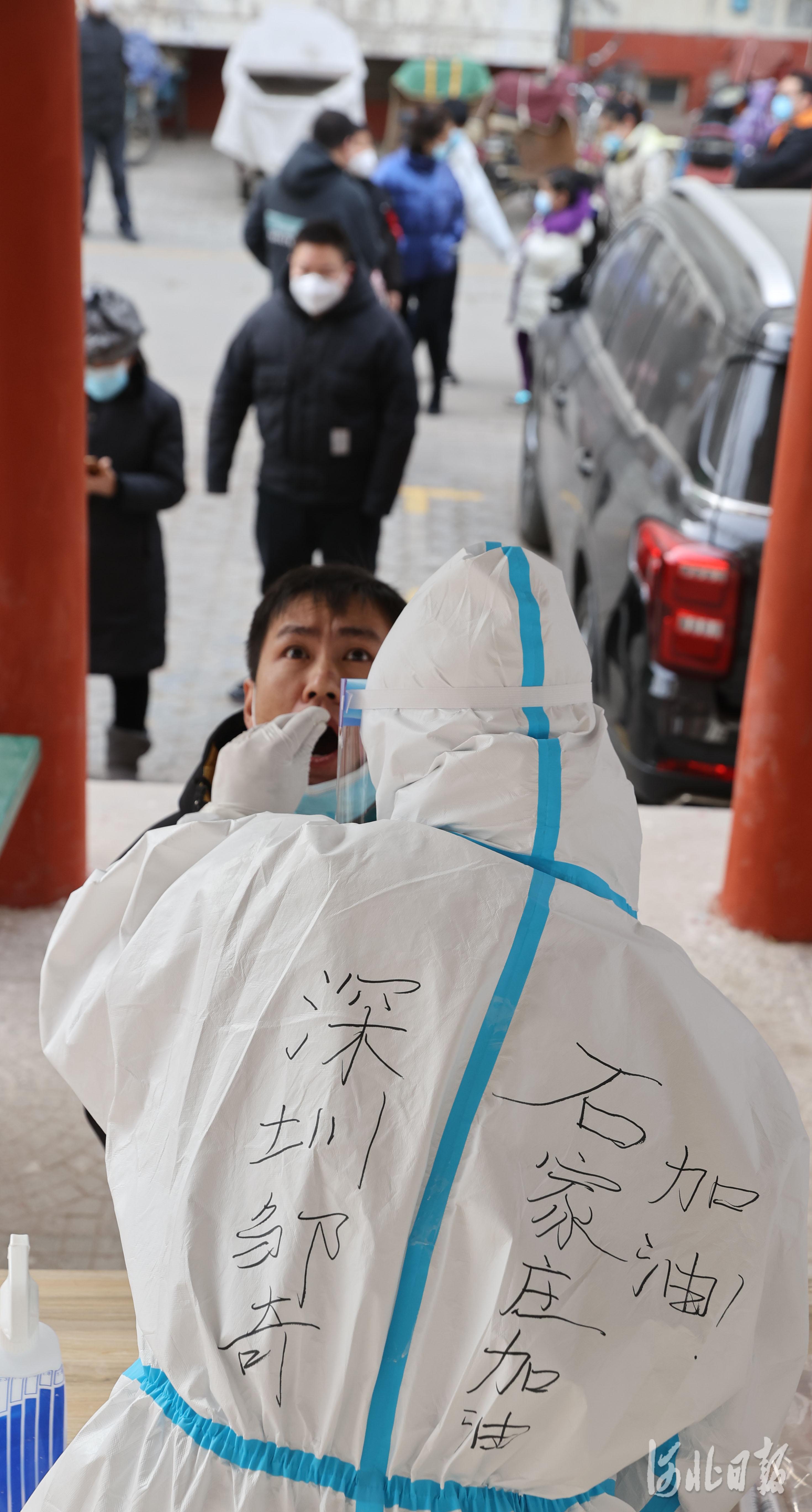 2021年1月12日,来自广东深圳核酸检测服务队的采样人员给石家庄市新华区赵陵铺路街道党家庄社区的居民进行核酸检测。