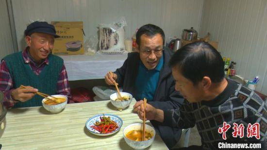 图为孙崇吉(中)与同事在驻守地吃饭。 周建辉 摄