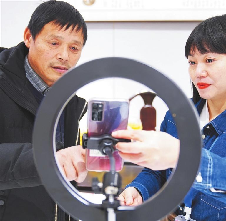 王冬生在主播玮玮的指导下与在线客户互动。